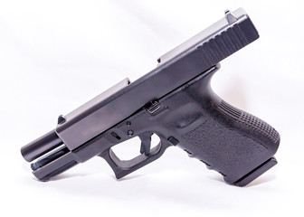 A black 9mm semi automatic pistol with an opened slide on a white background  Wall mural