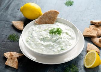 Tzatziki dip sauce with greek yogurt, garlic, dill and cucumber in white bowl