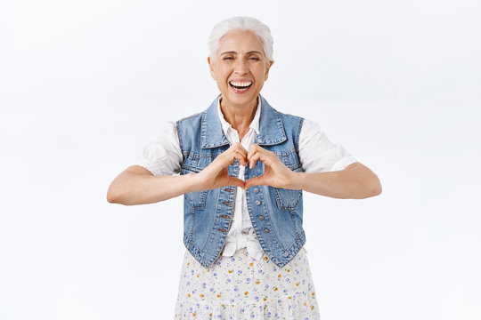 Modern, carefree charming old lady, senior woman showing heart sign and laughing, smiling joyfully, express care, tenderness and love, standing white background, cherish family holidays