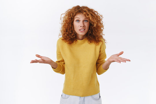 Girl apologizing, shrugging as dont know, cant help. Cute silly and awkward redhead woman in yellow sweater, spread arms sideways, smiling clumsy and embarrassed, admit her fault, white background