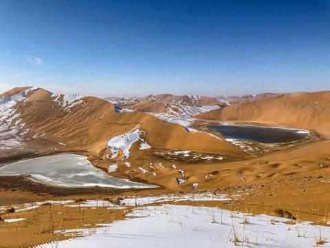 Yellow sand and white snow, and beautiful sky in Badain Jaran Desert, Inner Mongolia, China