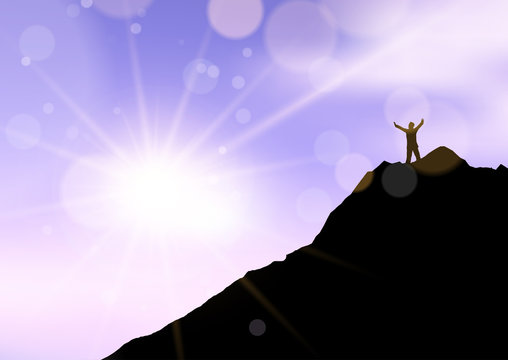 Silhouette of a male stood with arms raised on cliff edge against sunset sky
