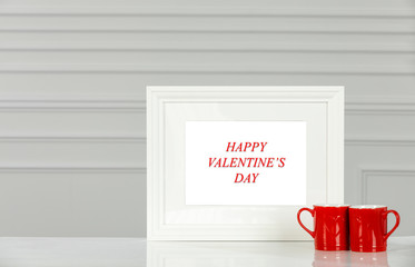 White frame of free space for your decoration on wooden table with white wall.Valentine's Day...