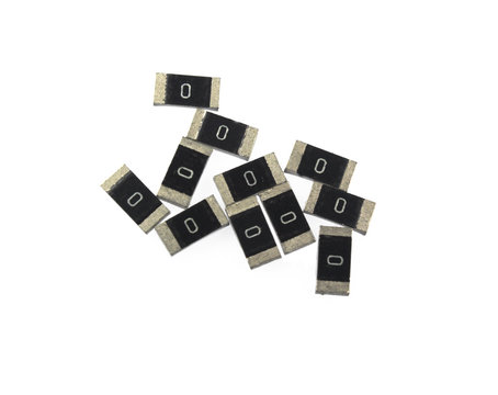 SMD resistors isolated on white background. On the body inscription value 0 Ohm