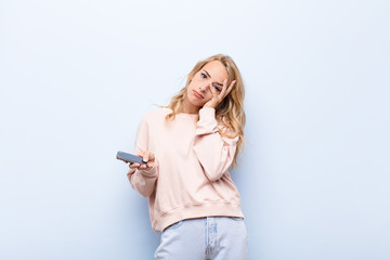 young blonde woman feeling bored, frustrated and sleepy after a tiresome, dull and tedious task, holding face with hand using a smartphone