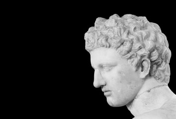 Black and white photo showing detail of male head of classical roman statue