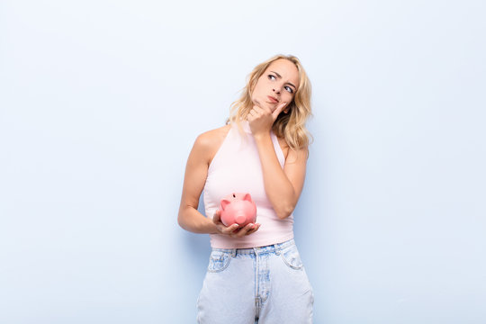 young blonde woman thinking, feeling doubtful and confused, with different options, wondering which decision to make holding a piggybank