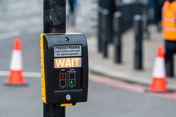 Crosswalk button for pedestrian with light warning on a defocused background , London, UK