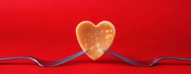 Creative breakfast for Valentine's Day. A pancake in the form of a heart is held in two forks, on a red background.Valentine's day background. Copy space