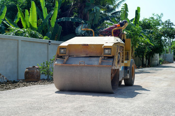Worker drives the road roller on the crash stone road for preparaing the surface