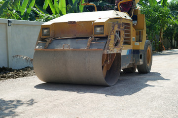Closeup heavy steel wheel of the road roller moving on the crash stone road under construction