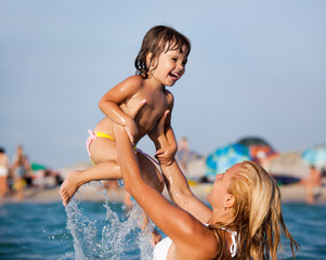 Young blond mother in white bikini standing in water and playing with her small smiling daughter on sunny summer day with beach at background. Family vacations and travelling concept