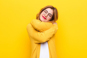 Fototapeta young pretty blonde woman feeling in love, smiling, cuddling and hugging self, staying single, being selfish and egocentric against yellow wall obraz