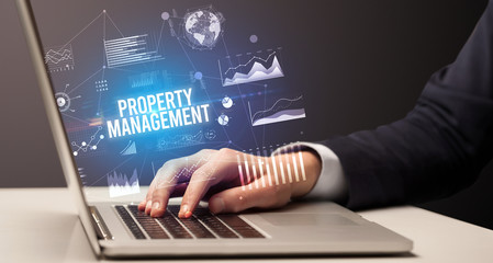Businessman working on laptop with PROPERTY MANAGEMENT inscription, new business concept