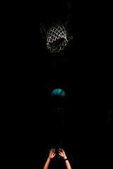 Cropped Image Of Hands Throwing Basketball Into Hoop At Night
