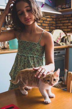girl with cat standing by table