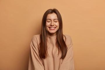 Portrait of beautiful woman with straight dark hair, smiles broadly, keeps eyes shut, enjoys pleasant moment, wears oversized brown jumper, expresses joy and happiness. Awesome emotions concept