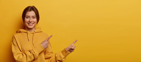 Check this out, better see it. Beautiful dark haired millennial girl wears casual hoodie, points both index fingers on blank space, has friendly smile, discusses promo, isolated on yellow background. Wall mural