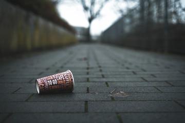 Leerer Kaffeebecher liegt auf Gehweg