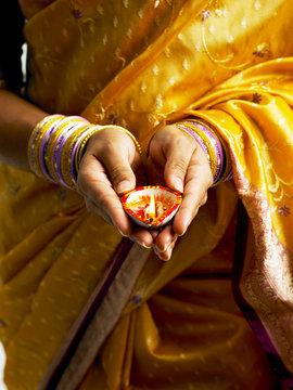 Midsection Of Woman Holding Diya