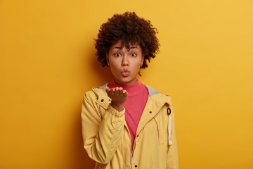 Romantic woman blows airkiss, keeps palms extended near mouth, sends mwah to boyfriend, has healthy skin, expresses her love, dressed casually, stands against vivid yellow background. Body language