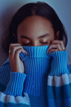 Close-Up Of Eyes Closed Young Woman Covering Face With Sweater Against Wall
