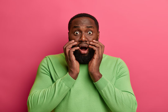 Frightened scared black man stares with popped eyes, witnesses disaster, gasps from shock, opens mouth widely, wears green jumper, widens eyes, isolated over vivid pink wall. What shocking rumors!