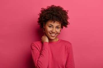 Good looking woman with curly hair, keeps hand on neck, smiles gently, wears crimson casual jumper, looks gladfully at camera, isolated over pink studio wall, has optimistic view. Happiness and joy