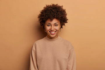 Modest relaxed healthy Afro American woman has tender toothy smile, enjoys lovely day, expresses...