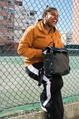 Smiling Young Woman With Bag Leaning On Chainlink Fence