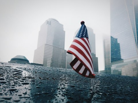 Low Angle View American Flag By Buildings During Rainy Season