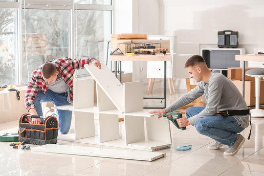Handymen assembling furniture in workshop