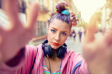 Playful cool rebel funky hipster young girl with headphones and crazy hair taking selfie on street