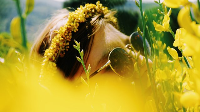 Close-Up Of Woman Wearing Sunglasses Amidst Yellow Flowers