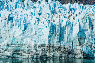 Close-up of Margerie Glacier where the dark lines are layers of rock formed from rock falls and streams that carry debris onto the ice.