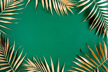 Wall Mural - Gold tropical palm leaves Monstera on green background. Flat lay, top view minimal concept.