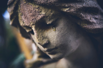 Fototapete - Death concept. Close Up of ancient statue of crying angel with tears in face as symbol of end of human life.