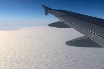 fly over a closed cloud cover with the airplane wing in the picture