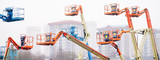Access platform equipment powered high in sky in blue orange and yellow for high working platform height safety at construction building site