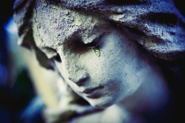 Fototapete - Death concept. Close Up of ancient statue of crying angel with tears in face as symbol of end of human life. Selective focus on eyes.