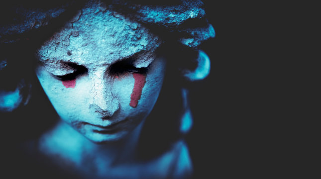 Death concept. Close up fragment of ancient statue of crying angel with tears in face as symbol of end of human life. Selective focus on eyes.