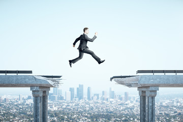 Businessman jumping over gap in bridge