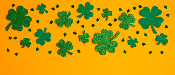 Shamrock four and three leaf clovers frame border on orange background. Happy St. Patrick's day concept
