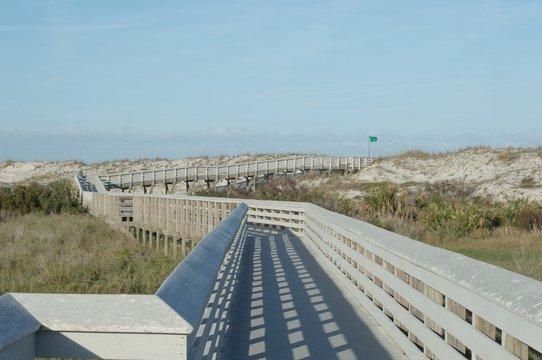 Boardwalk Over Field Against Clear Blue Sky