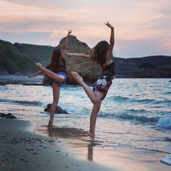 Teenage girls standing on one leg at beach