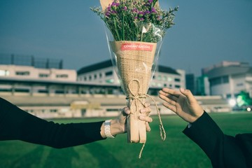 Cropped Image Of Man Giving Bouquet To Woman At Stadium