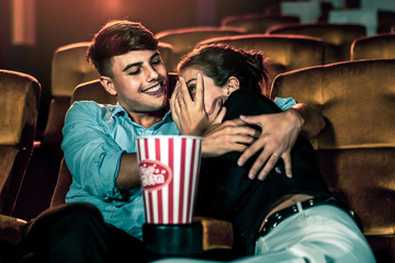 A couple of caucasian watch a thriller movie in the cinema, woman eyes closed and turning her face away from the screen