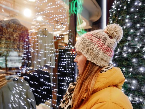 Side View Of Woman Looking At Clothes In Display Cabinet During Winter