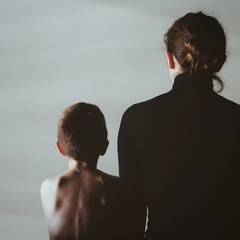 Rear View Of Mother With Shirtless Son Standing Against Sky