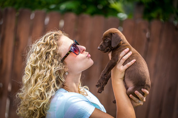 Young woman with sunglasses holds up brown lab vizsla mix and puckers for kiss